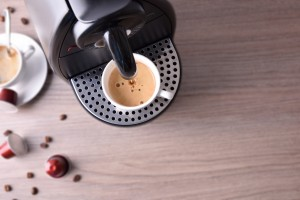 Expresso coffee machine with capsules and coffee served background on wood table. Top view