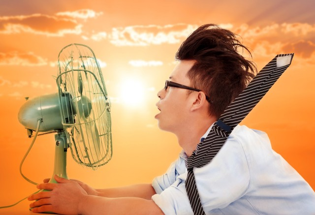 heat wave coming,business man holding a electric fan